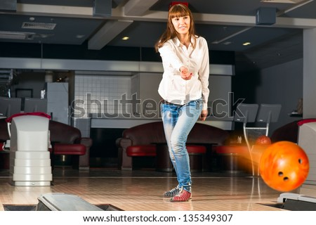 pleasant young woman throws a bowling ball, looks at the target and smiling - stock photo
