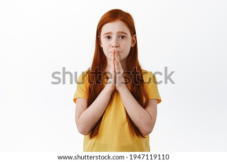 Please. Cute little girl making coy needy face and asking for something, begging to buy toy, pleading with hands in pray, staring with sad eyes at camera, white background Stock photo ©