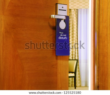 Please do not disturb sign hanging on open door in a hotel