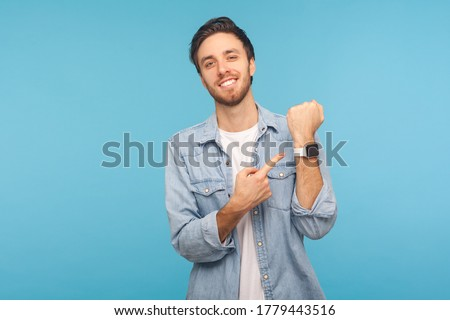 Please, hurry up! Portrait of cheerful punctual man in worker denim shirt pointing at wrist watch and smiling, showing smartwatch devise with mock up display. indoor isolated on blue background Stock photo ©