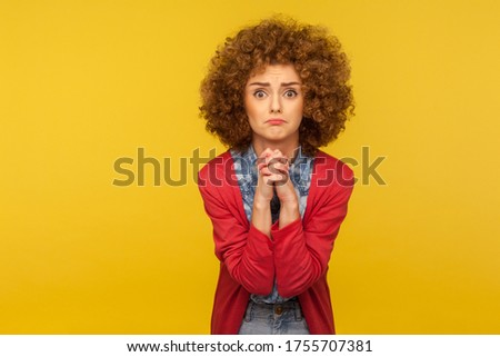 Please, I'm begging forgive! Portrait of upset worried woman with curly hair looking with imploring desperate grimace and praying for help, asking apology. studio shot isolated on yellow background Foto stock ©
