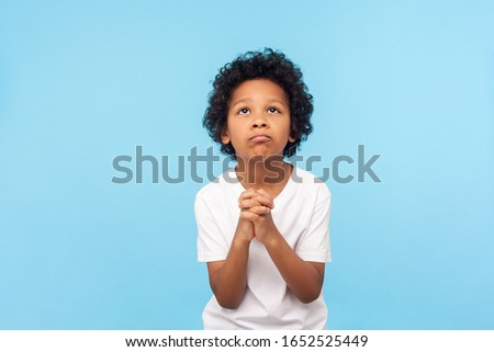 Please, I'm begging. Portrait of upset little boy praying to god with hands held together, apologizing for bad behavior, looking up with imploring eyes. indoor studio shot isolated on blue background Foto stock ©