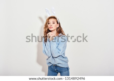 Please, please Cute playful girl wearing bunny ears has pleased expression isolated over white background
