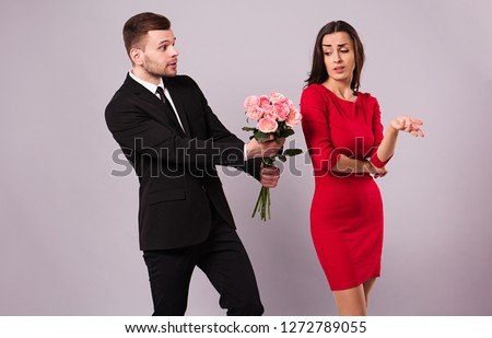 Please take it! I'm so sorry. Young elegant woman ignore the apologize of her boyfriend. Bad gift or present