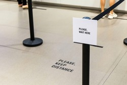Please wait here and keep distance  sign in front of purchase counter in department store for people to wait in line. New normal for prevent and stay safe from Corona virus or Covid-19.