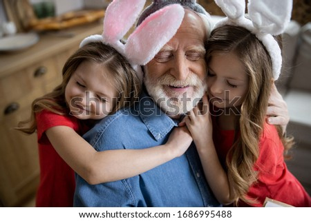 Pleased aged man smiling with closed eyes while granddaughters hugging him Stockfoto ©