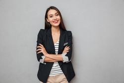 Pleased asian business woman with crossed arms looking at the camera over gray background