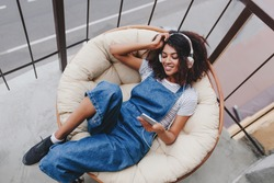 Pleased black girl wearing trendy sport shoes chilling on chair on balcony, enjoying morning alone. Portrait of smiling cute young woman in denim clothes having fun on terrace in weekend.