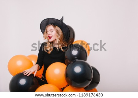 Pleased blonde woman with red lips preparing for halloween party with black and orange helium balloons. Indoor photo of joyful curly girl wears wizard attire isolated on white background.