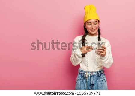 Pleased brunette Korean girl blogger texts sms during messaging with followers, edits media file, uses smartphone application, keeps hand on chest, touched to receive invitation to meet from friend #1555709771