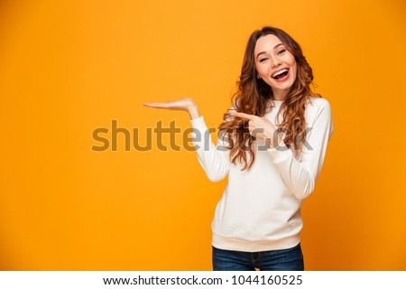 Pleased brunette woman in sweater holding copyspace on the palm and pointing on it while looking at the camera over yellow background