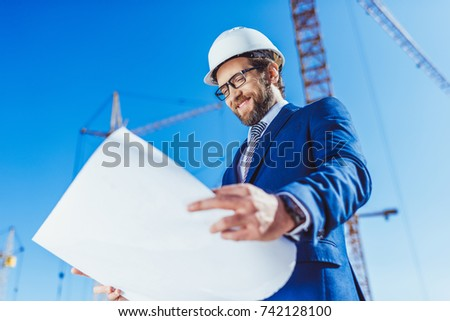 Pleased businessman in hardhat and suit looking at building plans at construction site