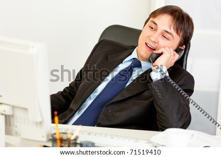 Pleased businessman sitting at office desk and talking on phone
