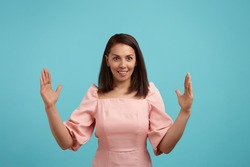 Pleased cheerful smiling european woman with dark hair in pink dress makes big sign with both hands, shapes quite huge object, impressed by size, shapes huge box, isolated on blue background
