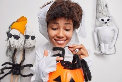 Pleased cheerful young woman plays with spider touches its legs holds carved pumpkin wears ghost costume has spooky image poses against white background makes creepy creatures for halloween.