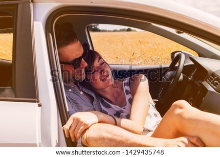 pleased couple enjoy the silence of the countryside embracing inside a parked car. relax, joy, freedom, love, togetherness and slow down concept.  #1429435748