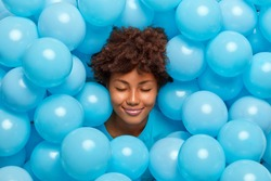Pleased curly haired woman closes eyes surrounded by many blue inflated balloons has festive mood has fun on party feels very happy. Afro American birthday girl keeps head through decorated background