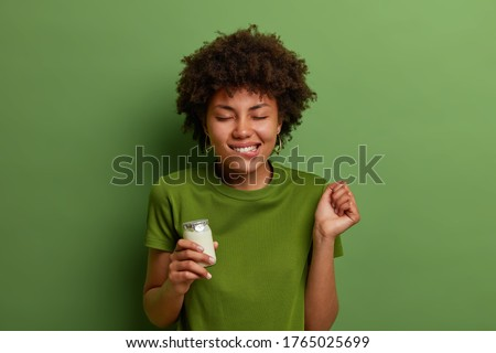 Pleased curly haired woman imagines taste of delicious fresh yoghurt, clenches fist and bites lips awaits for eating healthy product stands with closed eyes against green background. People, nutrition ストックフォト ©