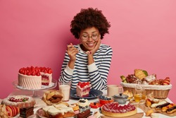 Pleased dark skinned woman tastes yummy strawberry cake, has good appetite, prepared various desserts for festive event, likes eating delicious food containing much calories, isolated on pink