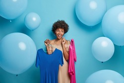 Pleased dark skinned young woman chooses stylish outfit to wear for date carries two dresses on hangers poses against blue background with inflated balloons around. People and fashion concept
