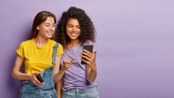Pleased female friends watch something interesting on mobile phone, have happy relaxed expressions, focused in device, enjoy using modern technologies, isolated over purple wall with empty space