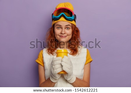 Pleased female skier has coffee break after active riding, wears white mittens, t shirt, yellow hat and protective snowboarding glasses, smiles with dimples, isolated over purple background.