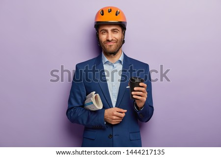 Pleased foreman wears orange helmet, elegant suit, drinks takeout coffee, carries newspaper, going on meeting with partners to discuss construction of new building. Architecture and business concept