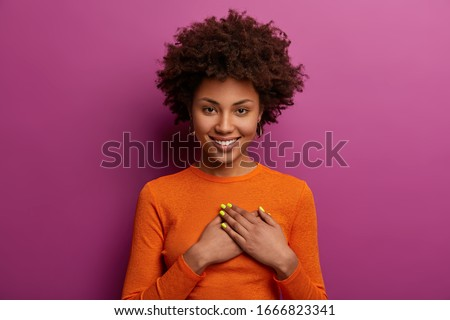 Pleased girl in orange jumper presses palms to heart, makes thankful gesture, touched with cordial congratulations, smiles positively, isolated over purple background. Acknowledgement concept Foto d'archivio ©