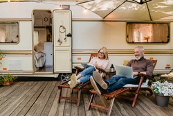 Pleased happy aged couple reading a book and using laptop while relaxing on the deck chairs near the camper van
