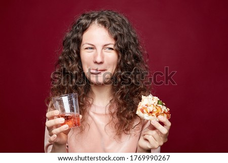 Photo of Pleased happy young woman gazes with happiness, looking aside at free space, eats pizza, shows direction, holding glass with bubble drink, shining with love, isolated over crimson background.
