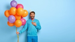 Pleased male celebrates getting new work, has office party with colleagues, feels thankful to receive congratulation, holds bunch with many colorful balloons has real holiday, blank space on blue wall