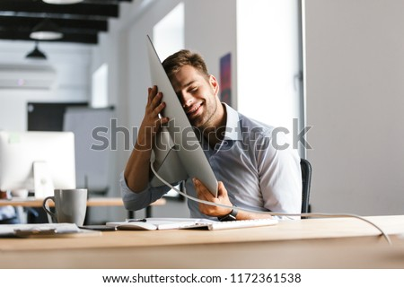 Pleased male manager having fun with computer while sitting by the table in office