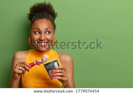 Pleased millennial girl with curly hair, bites lips and eats delicious ice cream with appetite, enjoys natural flavor, chills during summer day, looks gladfully aside, empty space on green background