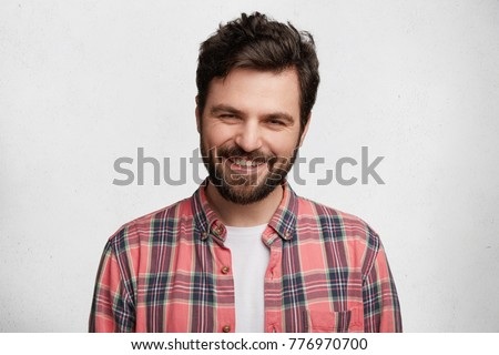 Pleased pleasant looking young student with beard and trendy hairdo wears casual checkered shirt, smiles pleasantly in camera, glad to pass session sucessfully, isolated over white background #776970700
