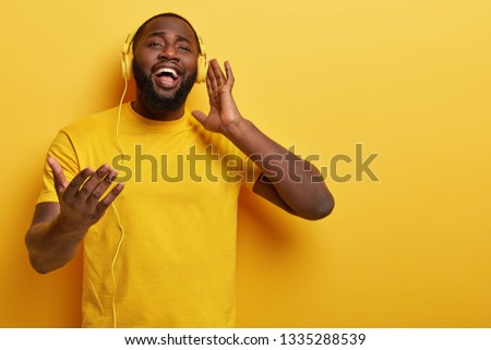 Pleased plump bearded dark skinned man listens romantic song in modern headphones, sings words and gestures with hand, wears yellow t shirt, picks melody for listening on way to work, feels glad