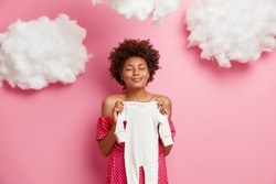 Pleased pregnant woman holds baby romper over tummy, prepares child clothes, stands with closed eyes, gets ready for maternity hospital, poses against pink background with clouds. Motherhood concept