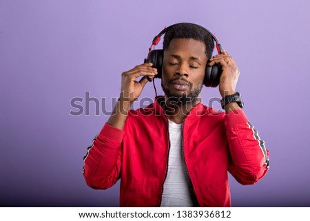 Pleased relaxed bearded stylish dark skinned man listening romantic song in modern black headphones, enjoying with closed eyes on violet background. Positive emotions, enjoyment, music. #1383936812