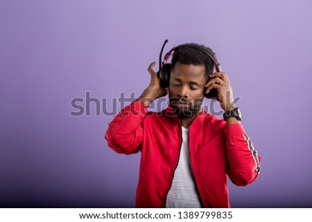 Pleased relaxed bearded stylish dark skinned man listening romantic song in modern black headphones, enjoying with closed eyes on violet background. Positive emotions, enjoyment, music. #1389799835