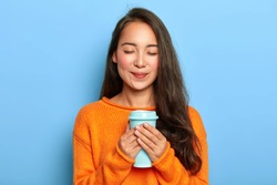 Pleased restful girl with Asian appearance, keeps eyes closed, smiles gently, enjoys drinking aromatic espresso from takeout cup, wears orange jumper, isolated over blue background. People and drink
