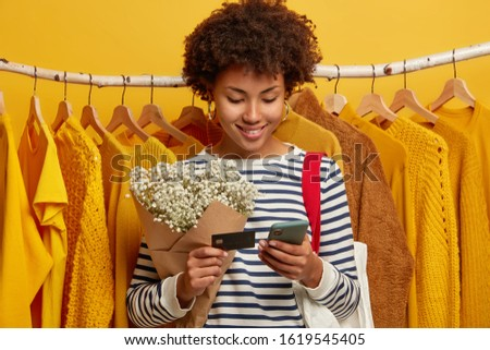 Pleased shopaholic stands near variey of clothes on hangers, buys garment online or pays for purchase with creadit card and mobile phone application, holds bouquet, wears striped jumper. Payment