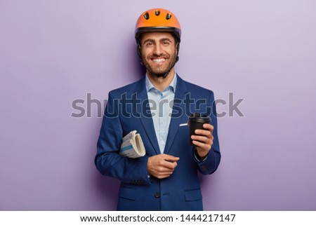 Pleased smiling architect has coffee break, holds disposable cup with beverage, newspaper under arm, rejoice success at work, wears formal clothing, orange cyclist helmet, being in good mood