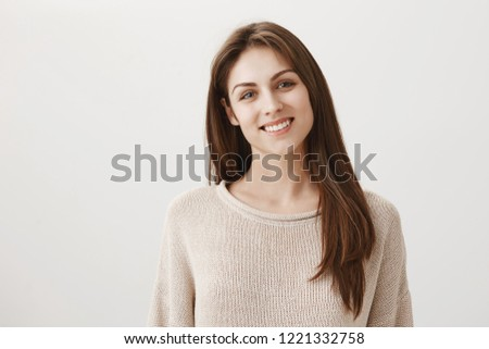 Pleased to help you. Portrait of polite good-looking office assistant standing in warm sweater and smiling broadly, wanting to help or offer coffee to customer tilting head, hearing out order