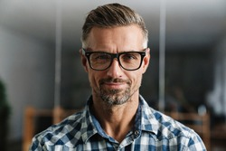 Pleased white-haired man in eyeglasses smiling at camera while standing in office