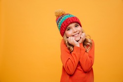 Pleased Young girl in sweater and hat reclines on her arms and looking at the camera over orange background