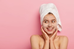 Pleased young woman with delighted expression, applies natural beauty product on face, uncloges pores, has charming smile, looks aside, has wrapped towel on head, has naked body, healthy skin