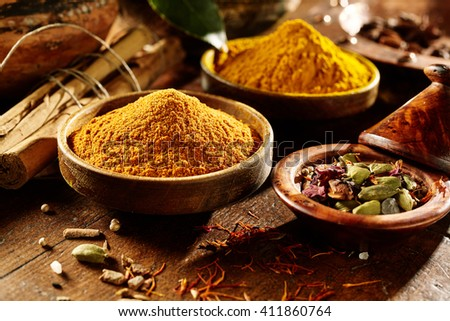 Pleasingly lit wooden table with ground and whole curry powder and turmeric in bowls beside hard bamboo sticks
