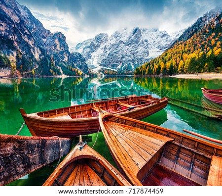 Pleasure boats on Braies Lakeand Seekofel mount on background. Colorful autumn landscape in Italian Alps, Naturpark Fanes-Sennes-Prags, Dolomite, Italy, Europe. Artistic style post processed photo.