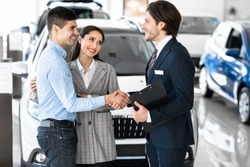 Pleasure Working With You. Beautiful couple embracing after buying new car, shaking hands with salesman