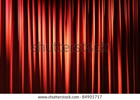 Pleated, red, hanging fabric stage curtain.