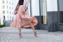 Pleated skirt coral color and sneakers. The girl is very dynamic posing on the street, the skirt is developing.